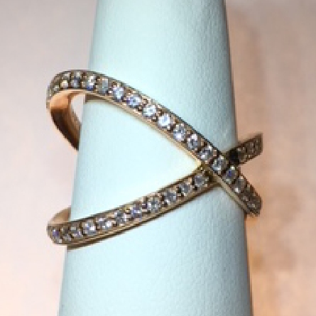 14 karat rose gold negative space ring; shared prong settings on two interlocking bands forming an off-center X; .57cttw diamond