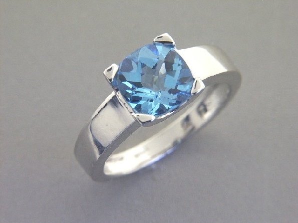 14K white gold ring; 8mm checkerboard cushion blue topaz prong set on wide polished tapered shank