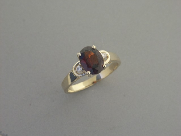 14K yellow gold ring; prong-set 9x7mm oval faceted garnet with one prong-set diamond on each side with raised frame