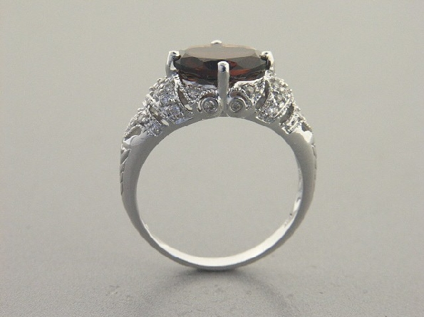 14K white gold ring; 10x8mm oval garnet prong-set east-west; filigree upper shanks bead-set with .27cttw dia.