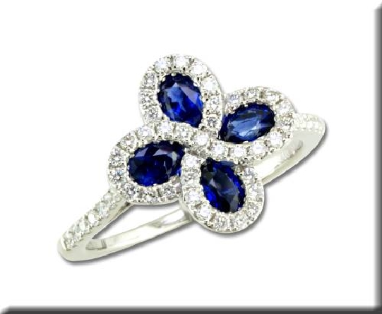 14 karat white gold ring; 4 oval blue sapphires pointing to the center; swirled halo of diamonds around each sapphire; diamonds down each side shank