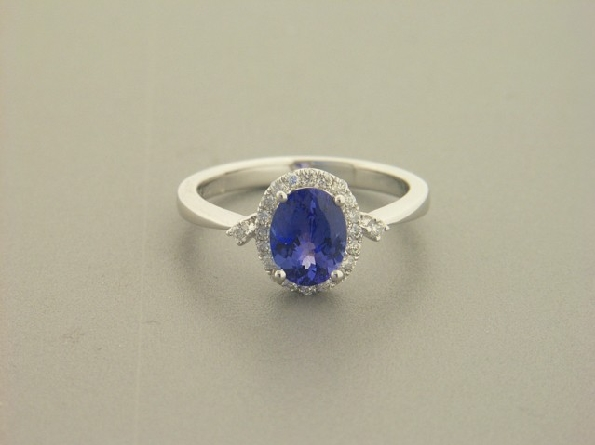 14 karat white gold ring; better quality oval tanzanite weighing 1.22carat surrounded by a diamond halo; one diamond at the top of each straight pinched shank; .20cttw diamond