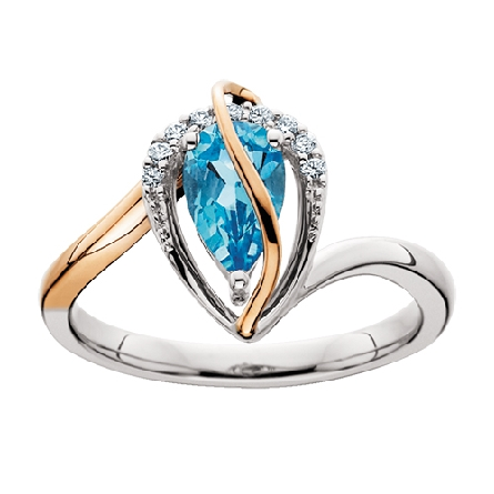 10 karat two tone ring; center is pear shaped blue topaz with diamond-set open pear shaped frame; .06cttw; offset shank is white gold on one side; rose gold on the other; rose gold ribbon curves over top of topaz