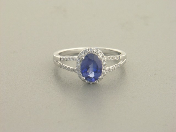 14 karat white gold ring with 6x8mm oval tanzanite center weighing 1.22 carat; with diamond halo and diamonds down split shanks .18cttw diamond