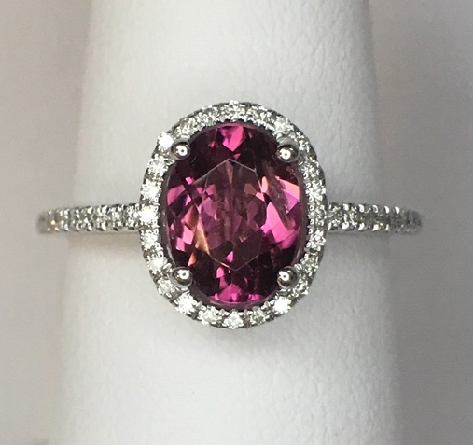 14 karat white gold ring with deep pink oval tourmaline surrounded by diamonds; diamonds on cathedral shanks; open heart design undercarriage. tourmaline = 1.19 carat; diamonds = .17cttw