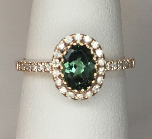 14 karat rose gold low-profile ring with oval green tourmaline center; diamond halo and diamonds on side shanks. Tourmaline = .89 carat; diamonds = .21cttw