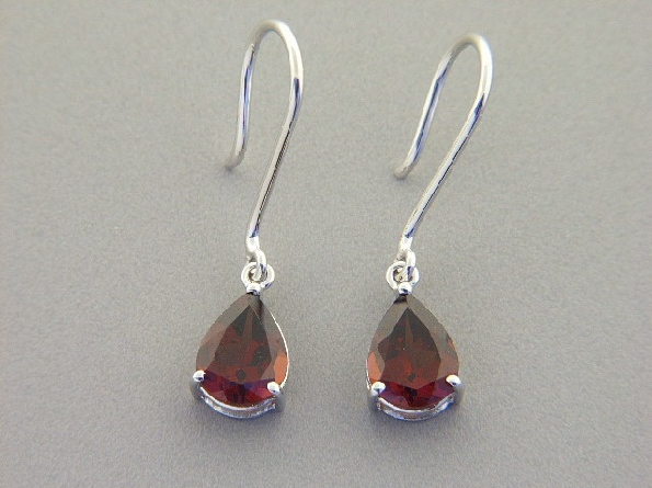 14 karat white gold earrings; 6x8 pear shaped garnet dangle on French wire