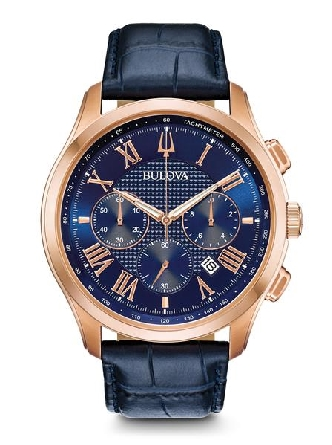 From Bulova s Classic Collection. New Wilton style with six-hand chronograph function. Rose gold-tone stainless steel case with applied Roman markers; tachymeter and calendar feature on dark blue textured dial; domed mineral glass; croco-embossed blu