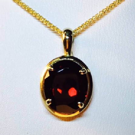 14 karat yellow gold pendant with 12x10 oval garnet; four prong setting with polished frame; single enhancer (hinged) bail; on 18 inch wheat chain